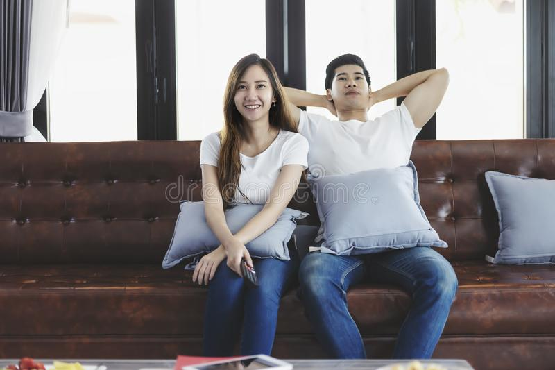 Happy asian young couple loving on the couch watching a movie together stock photo