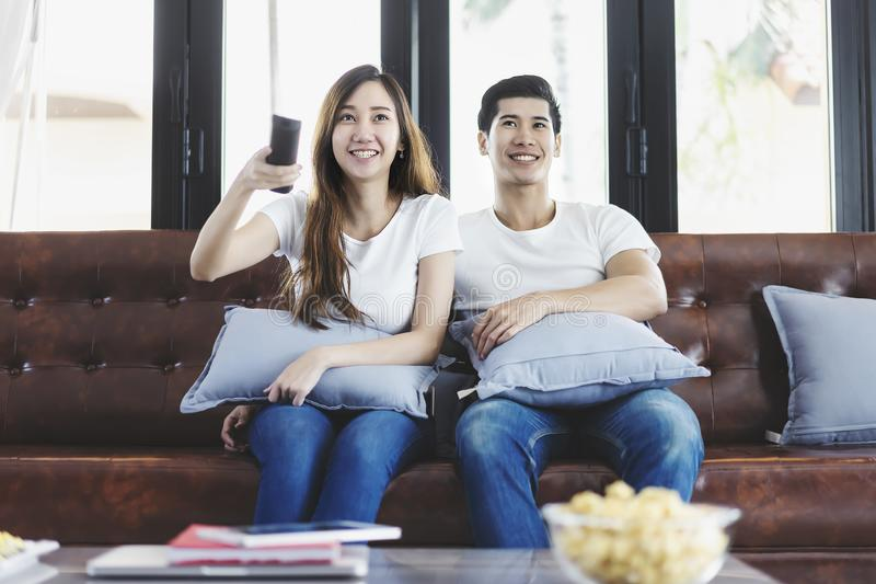 Happy asian young couple loving on the couch watching a movie together stock photography