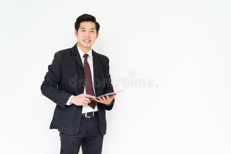 Happy asian young handsome businessman using tablet royalty free stock photo