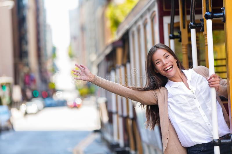 Happy Asian young woman excited having fun riding the popular tourist attraction tramway cable car system in San Francisco city, royalty free stock photo