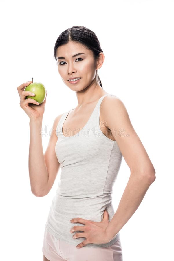 Happy Asian young woman holding a green apple stock photos
