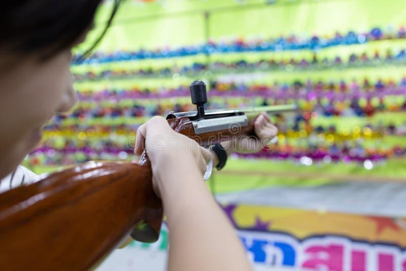 Happy asiatische Mädchen mit Holzpistole, zielen auf den Punkt, schießen das Ziel, Frauen spielen Drehspiele für den Karneval auf stockbilder