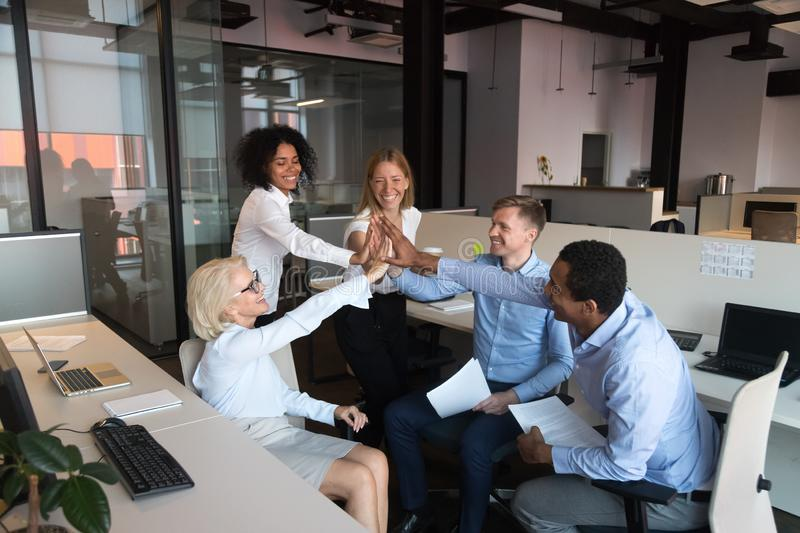 Happy associates giving high five after good deal celebrating success. Cheerful coworkers different ages and ethnicity gathered together in coworking shared royalty free stock photo