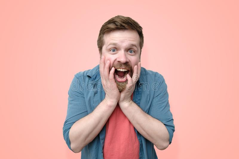 A happy, astonished Caucasian man with a beard, emotionally holds his hands on his face and opened his mouth from a pleasant stock photography