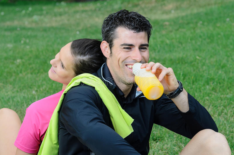 Happy Athletes. Couple of happy athletes taking a break, and smiling while the male drinks orange juice royalty free stock images