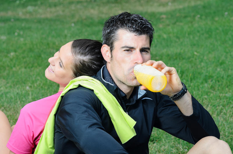 Happy Athletes Drink. Couple of happy athletes taking a break, and smiling while the male drinks orange juice and women rests on the man's back royalty free stock photos