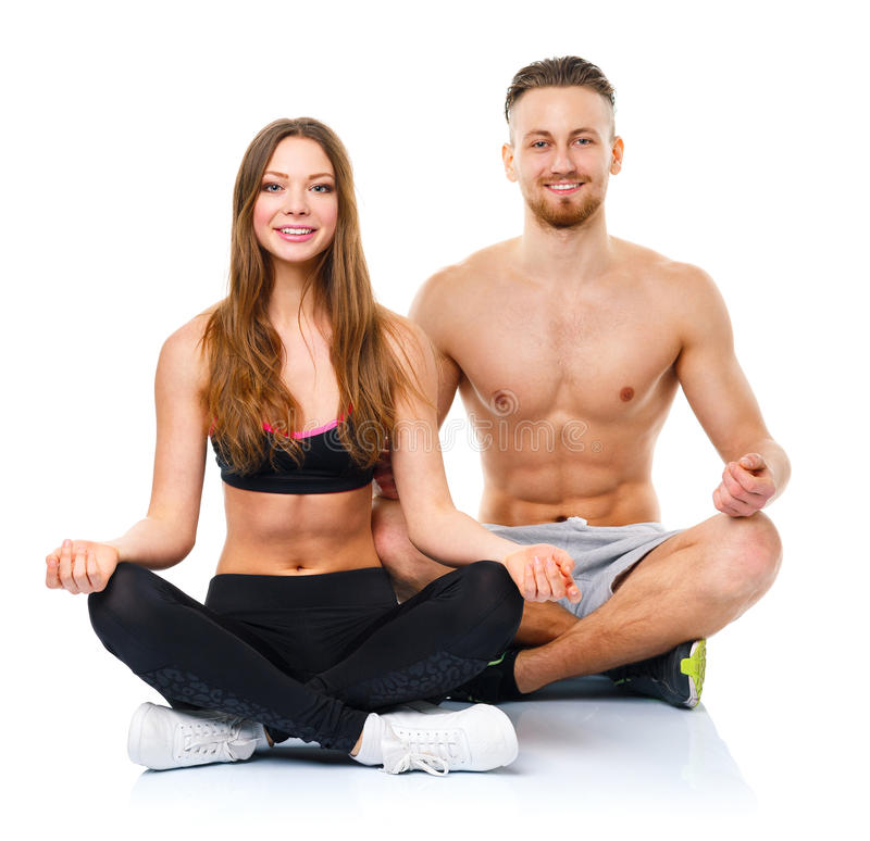 Happy athletic couple practicing yoga, doing exercise for relaxa stock image