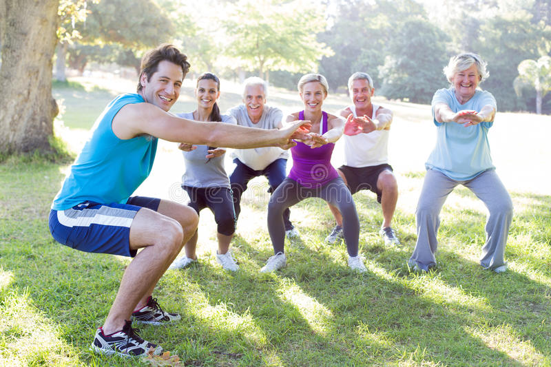 Happy athletic group training. On a sunny day royalty free stock image