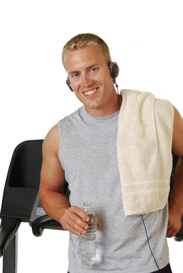 Happy athletic man leaning against a treadmill royalty free stock photo