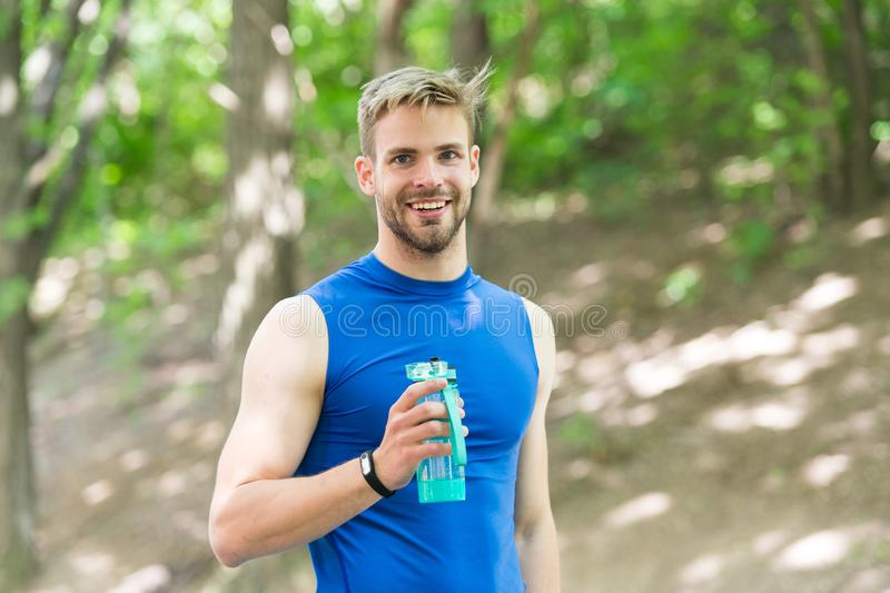 Happy athletic man with water bottle. Athlete drink water after training in park. body hydration. sport and health. man stock image