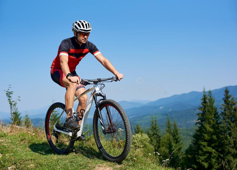 Happy athletic tourist cyclist in helmet, sunglasses and full equipment riding bike on grassy hill. Mountains and blue summer sky on background. Active stock images
