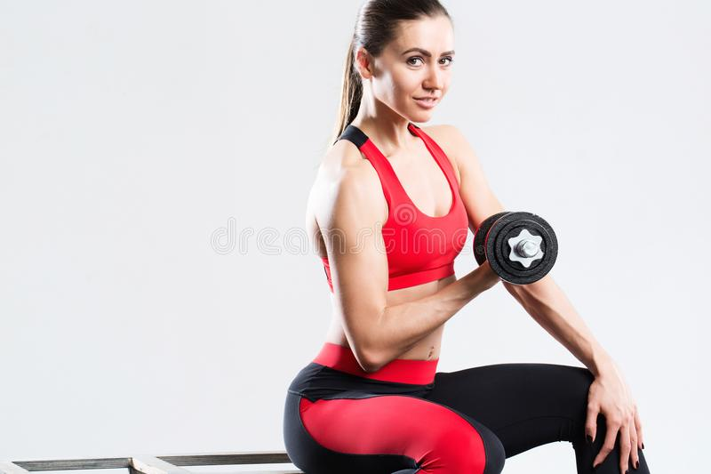 Happy athletic woman with dumbbells doing sport exercise, isolated on gray background. stock images