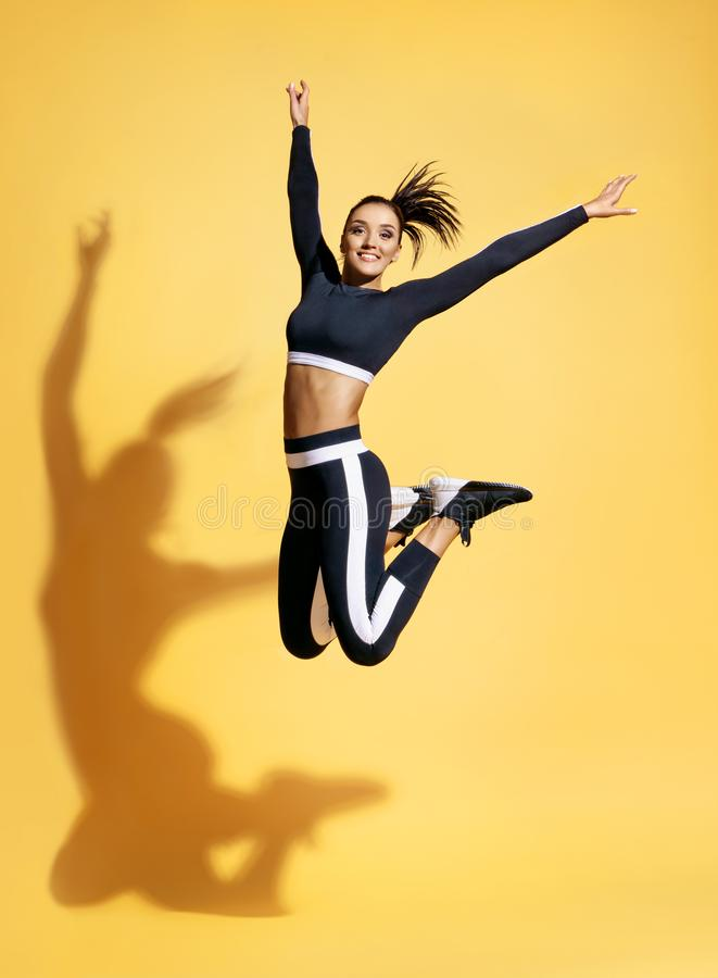 Happy athletic woman jumping up in silhouette. royalty free stock photography