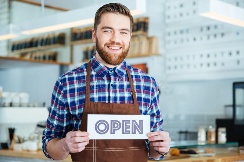 Happy attactive young barista holding open sign at coffee shop. Happy attactive young barista in plaid shirt and brown apron holding open sign at the coffee shop royalty free stock images