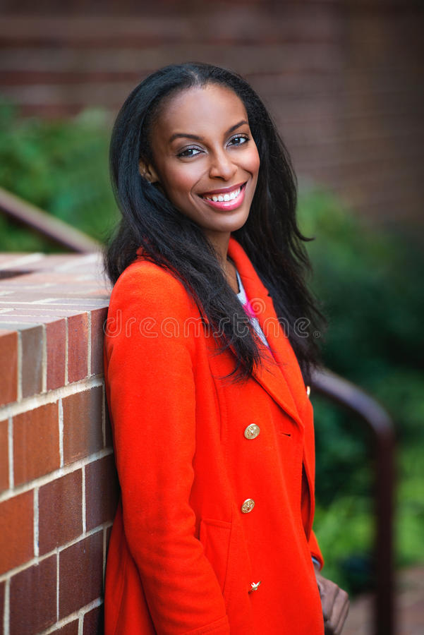 Happy attractive african american woman smiling outdoors wearing autumn outfit royalty free stock photography