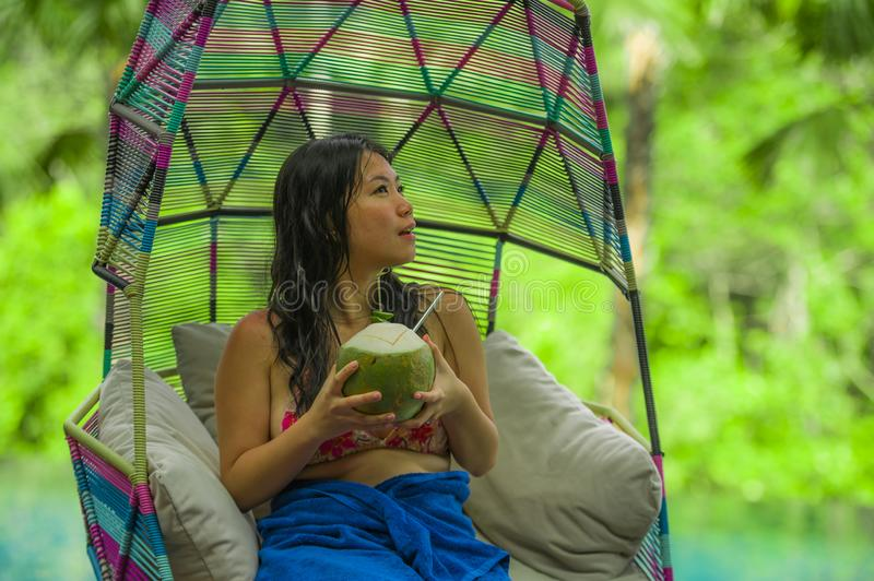 Happy and attractive Asian Chinese woman sitting at hanging hammock drinking coconut water relaxing at resort swimming pool. Young happy and attractive Asian stock photos