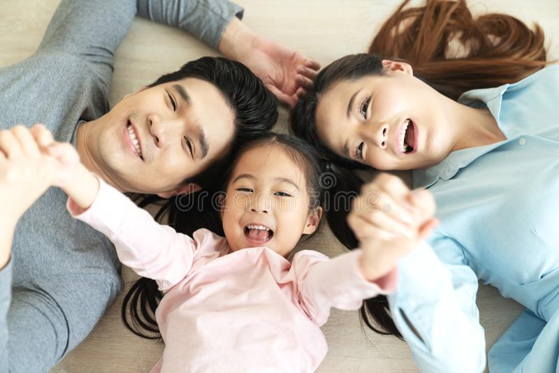 Happy attractive asian family with mom, dad and little cute young daughter or elementary kids holding hands together lying on stock image