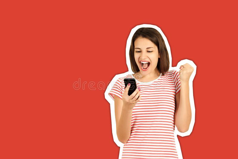 Happy attractive brunette girl joying win in video game on smartphone. emotional girl Magazine collage style with trendy color. Background stock photography