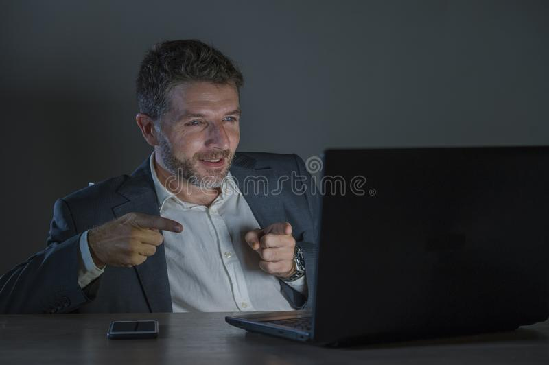 Happy and attractive businessman celebrating success in cheerful and excited face expression working late night at office laptop. Young happy and attractive stock photos