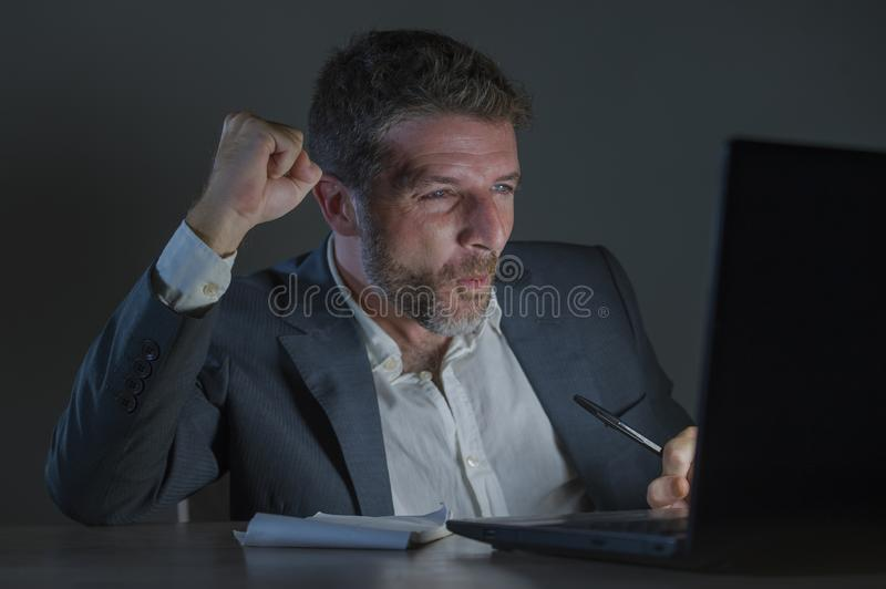 Happy and attractive businessman celebrating success in cheerful and excited face expression working late night at office laptop. Young happy and attractive royalty free stock photos