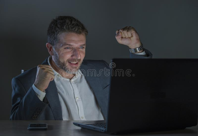 Happy and attractive businessman celebrating success in cheerful and excited face expression working late night at office laptop. Young happy and attractive royalty free stock images
