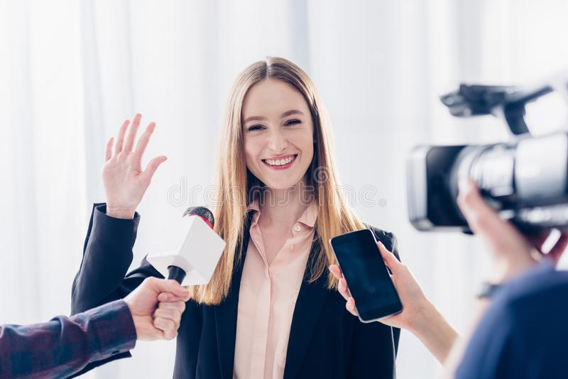 Happy attractive businesswoman giving interview to journalists and waving hand. In office royalty free stock image