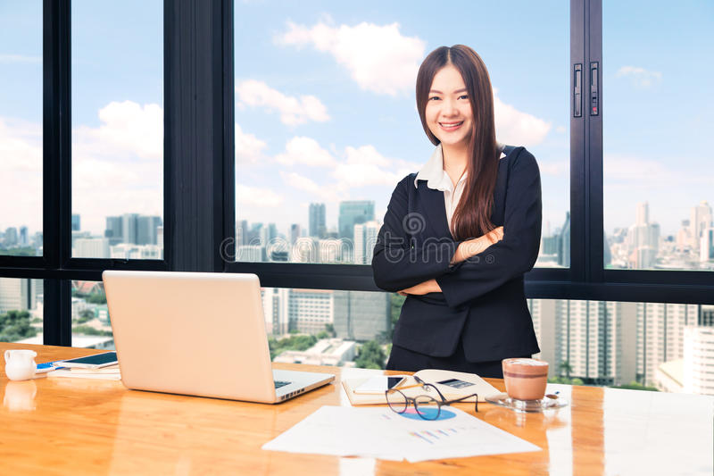 Happy attractive businesswoman standing in her office with city. Happy attractive businesswoman in suit standing behind her desk, with computer, other working royalty free stock photo
