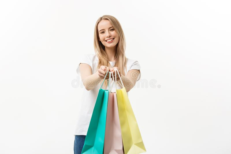 Happy attractive caucasian woman offering shopping bags over white background royalty free stock photography