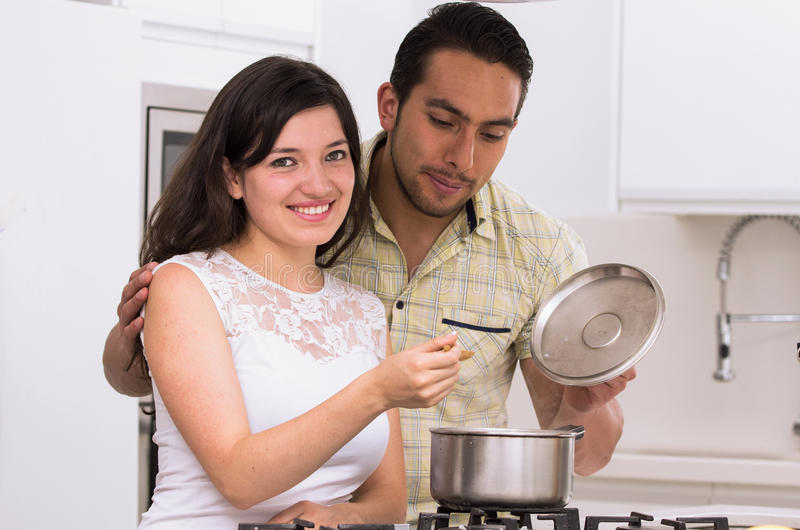 Happy attractive couple cooking together stock photography