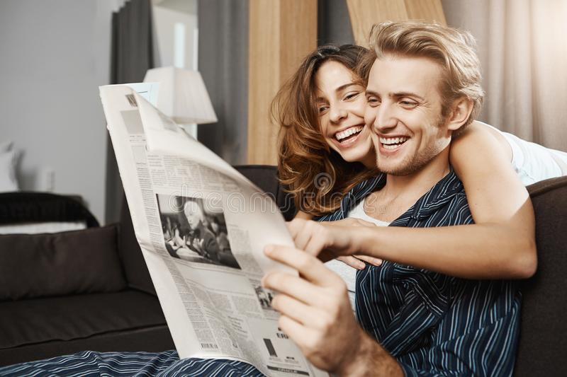 Happy and attractive couple in love reading newspaper at home and laughing sincerely while girlfriend hugging boyfriend royalty free stock image