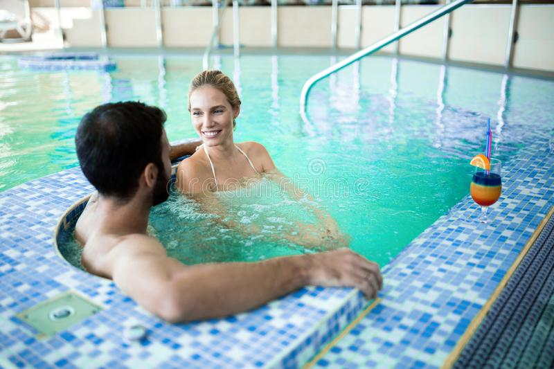 Happy attractive couple relaxing in swimming pool. Happy attractive couple relaxing in spa swimming pool stock image