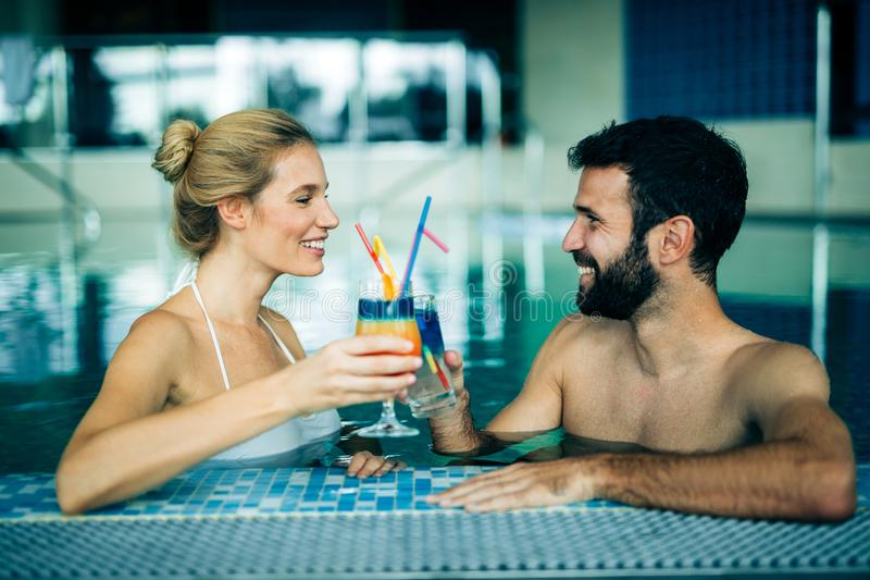 Happy attractive couple relaxing in swimming pool. Happy attractive couple relaxing in spa swimming pool royalty free stock image