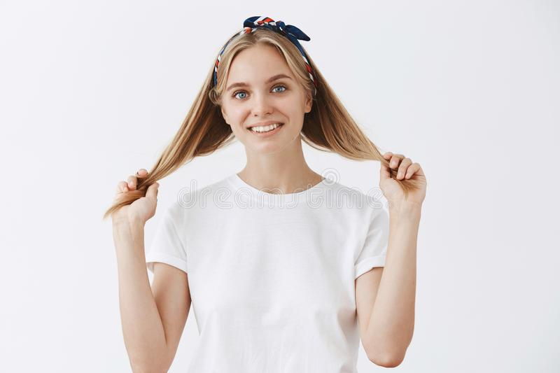Happy attractive and emotive blond woman in headband and white t-shirt pulling hair strands with hands and smiling royalty free stock photography