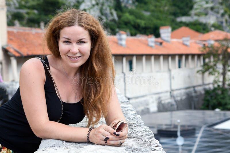 Happy attractive European woman portrait looking at camera, long hair, black shirt, copyspace. Walls of ancient fortress. Happy attractive European woman stock image