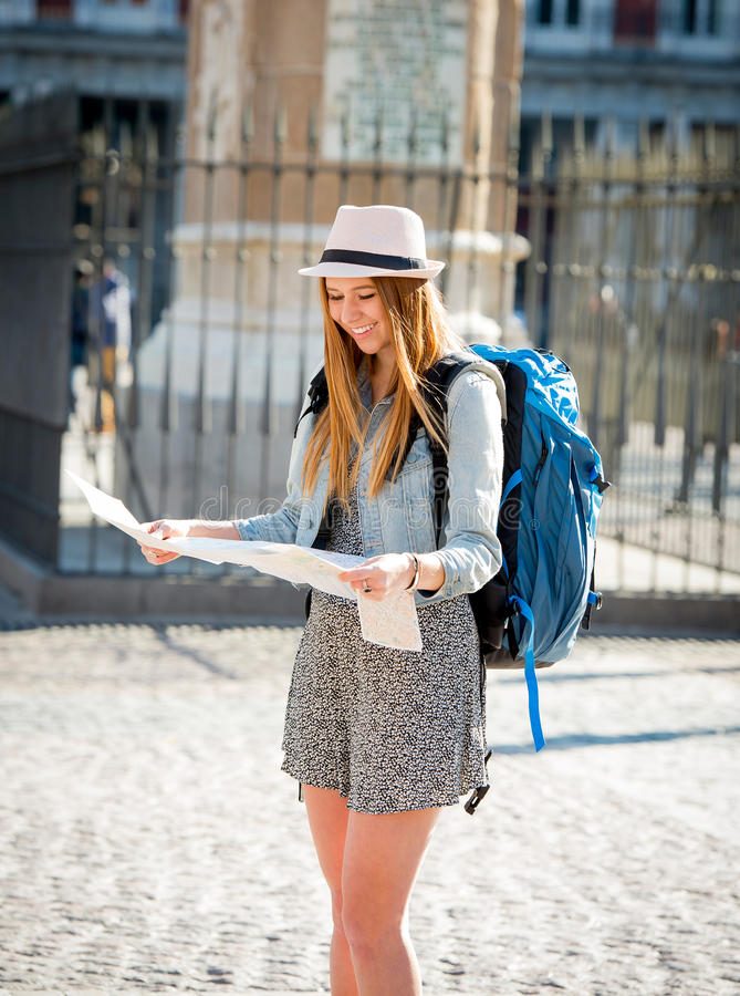 Happy attractive exchange student girl visiting Madrid city reading map royalty free stock photography
