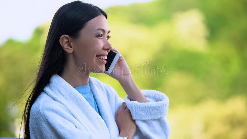 Happy attractive female in bathrobe talking on phone, luxury resort vacation royalty free stock photos