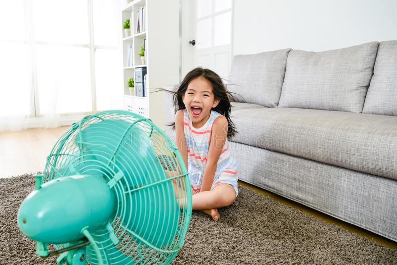 Happy attractive female kid blowing cooling wind stock photo