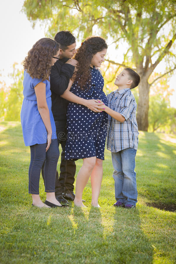 Happy Attractive Hispanic Family With Their Pregnant Mother Outdoors royalty free stock photos