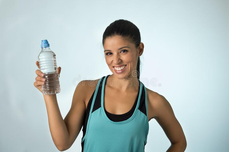 Happy and attractive latin sport woman in fitness clothes holding bottle drinking water smiling fresh and cheerful. Young happy and attractive latin sport woman royalty free stock images