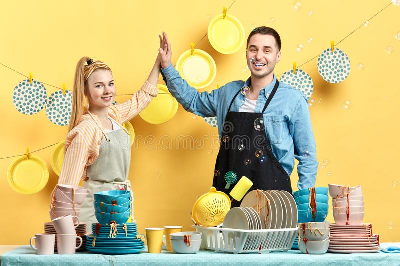 Happy attractive man and woman in aprons holding each other royalty free stock photography