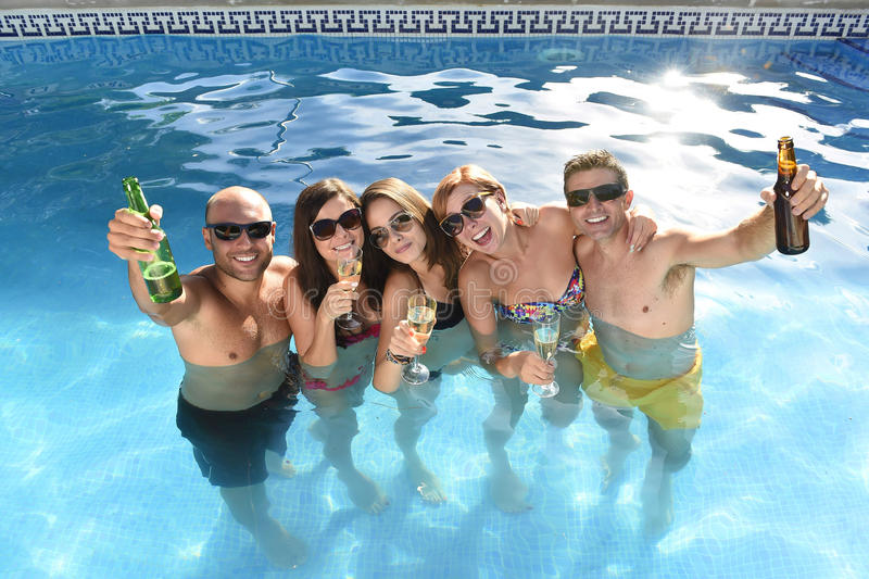 Happy attractive men and women in bikini having bath at hotel resort swimming pool drinking beer. Group of friends young happy attractive men and women in bikini royalty free stock photos