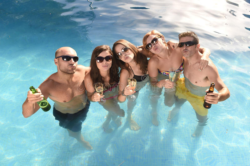 Happy attractive men and women in bikini having bath at hotel resort swimming pool drinking beer. Group of friends young happy attractive men and women in bikini stock photos