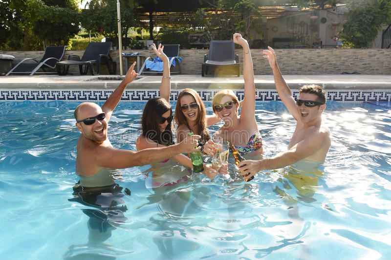 Happy attractive men and women in bikini having bath at hotel resort swimming pool drinking beer. Group of friends young happy attractive men and women in bikini royalty free stock image