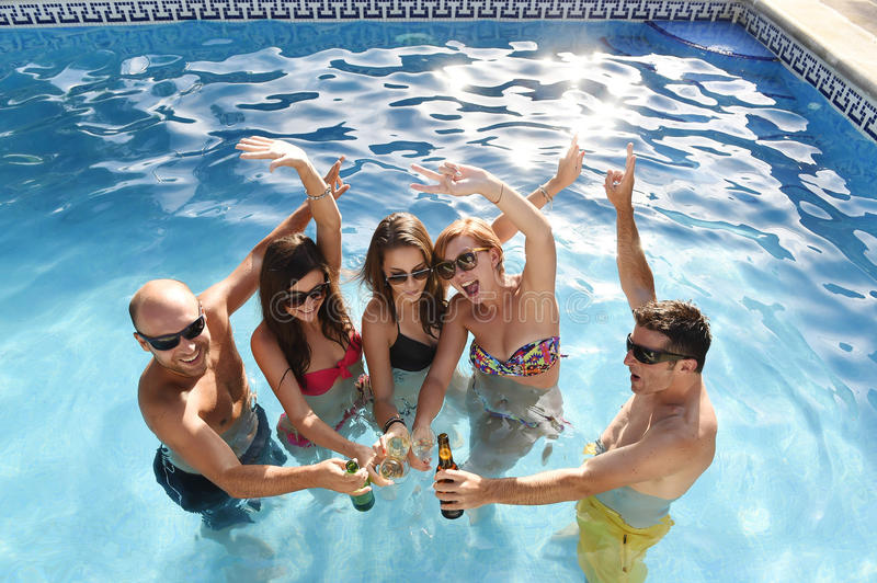 Happy attractive men and women in bikini having bath at hotel resort swimming pool drinking beer. Group of friends young happy attractive men and women in bikini royalty free stock photography