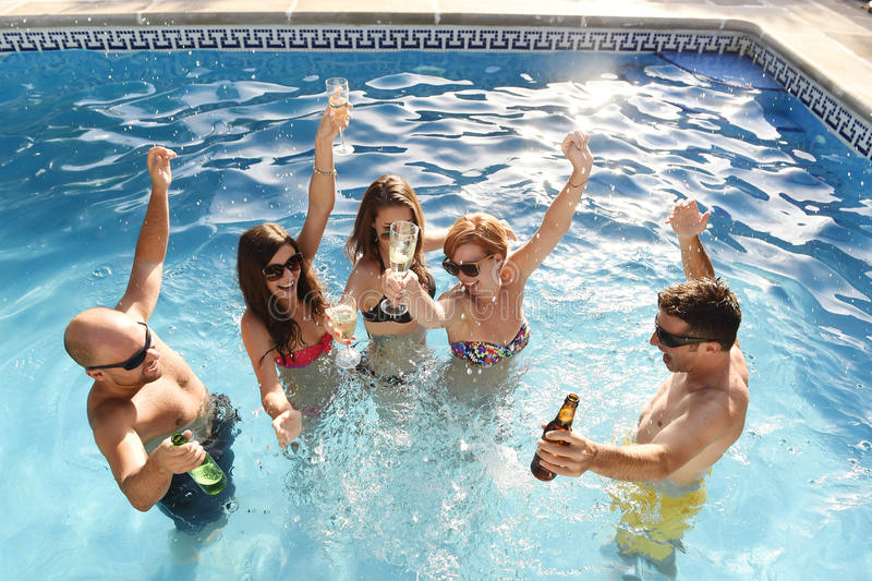 Happy attractive men and women in bikini having bath at hotel resort swimming pool drinking beer. Group of friends young happy attractive men and women in bikini stock photography