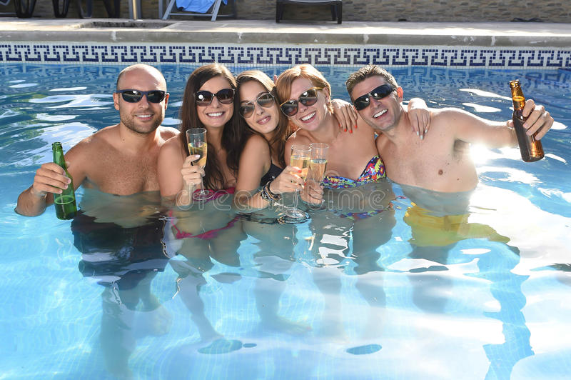 Happy attractive men and women in bikini having bath at hotel resort swimming pool drinking beer. Group of friends young happy attractive men and women in bikini stock image