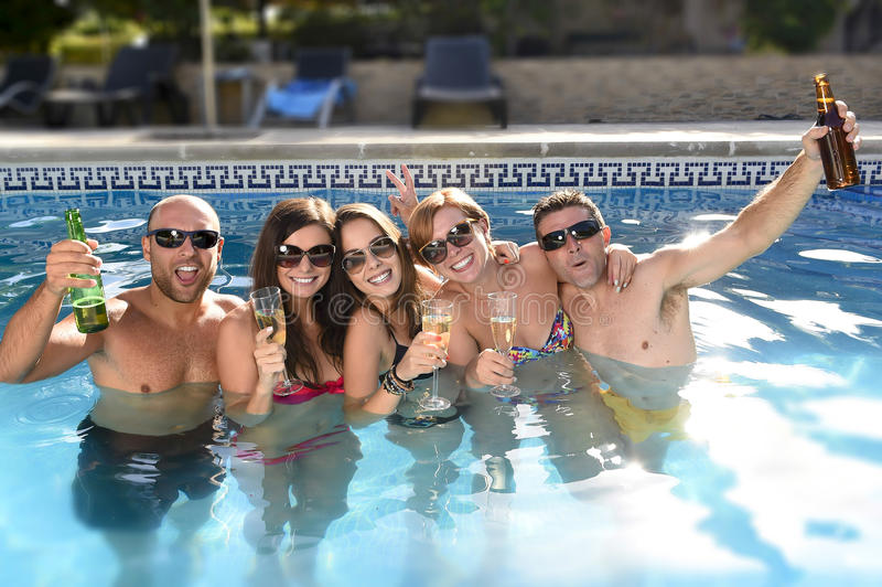 Happy attractive men and women in bikini having bath at hotel resort swimming pool drinking beer. Group of friends young happy attractive men and women in bikini stock photo