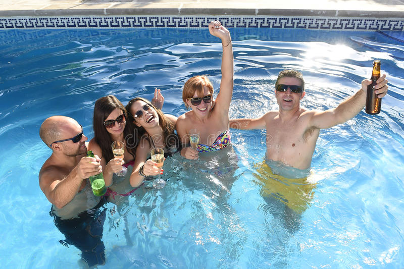 Happy attractive men and women in bikini having bath at hotel resort swimming pool drinking beer. Group of friends young happy attractive men and women in bikini stock images