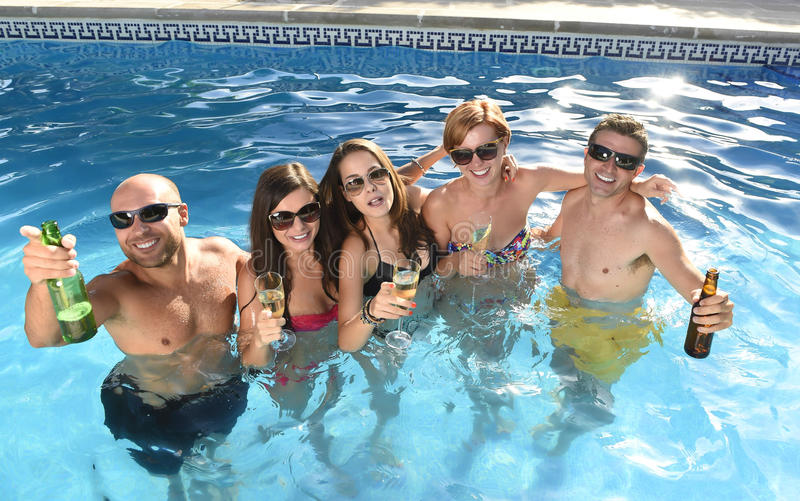 Happy attractive men and women in bikini having bath at hotel resort swimming pool drinking beer. Group of friends young happy attractive men and women in bikini royalty free stock photo