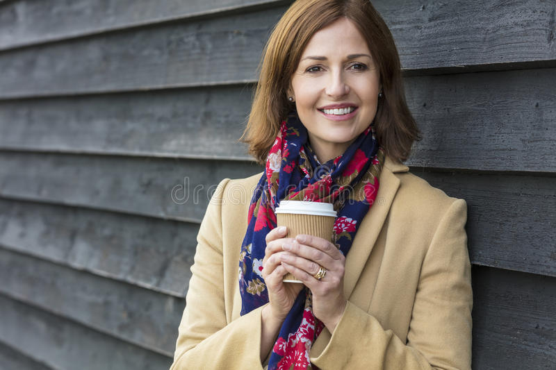 Happy Attractive Middle Aged Woman Drinking Coffee. Portrait shot of an attractive, successful and happy middle aged woman female outside drinking coffee in a royalty free stock photography